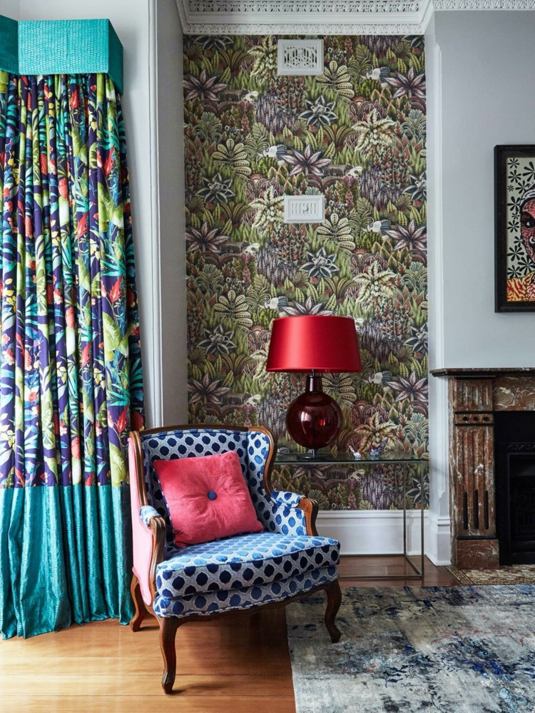 A blue chair with colourful curtains beside a red table lamp, Thrive E Magazine