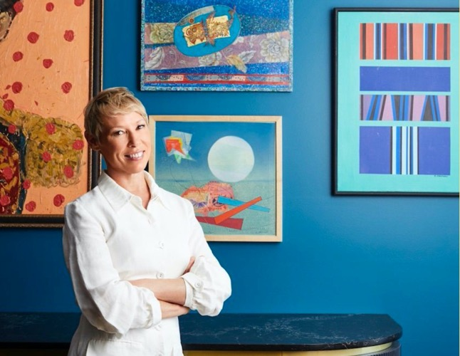 A woman in a white stress standing next to paintings on a blue wall, Thrive E Magazine